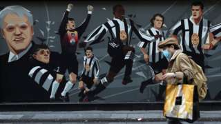 Man with mask walks past Newcastle United mural