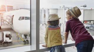 Children looking out of an airport window.