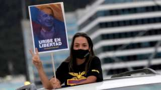 """A supporter of Alvaro Uribe, former president and legislator of Colombia, wearing a face mask, holds a sign that reads """"Uribe in freedom"""" during a protest against the house arrest measure ordered by the Supreme Court of Justice, against the former president in Bogota, Colombia August 7, 2020."""