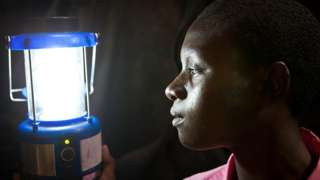 Person looks at solar powered lamp