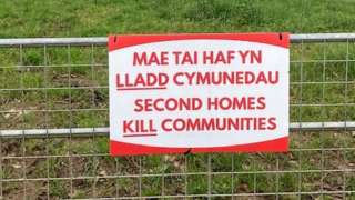 Second homes kill communities sign