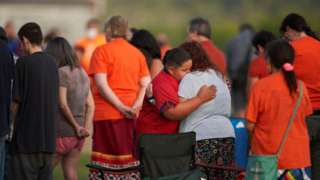People hug during a vigil in a field where human remains were found in unmarked graves at the site of the former Marieval Indian Residential School on the Cowessess First Nation in Saskatchewan on June 26, 2021