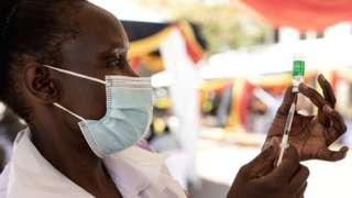 A Ugandan nurse draws a vaccine dose in Kampala