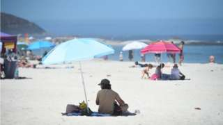 People sunbathing at Bay Beach in Cape Town, South Africa