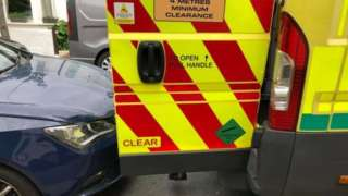 Car parked behind ambulance