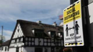 Social distance sign near Crown and Anchor pub