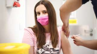 A person receives a dose of the Pfizer BioNTech vaccine at the Central Middlesex Hospital in London