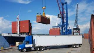 Container being lifted from a ship to a lorry