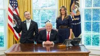 Nikos Giannopoulos with Donald and Melania Trump. and a flag