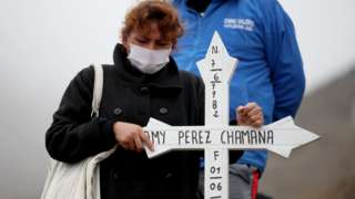 A relative of a Covid-19 victim prays in front of her grave in Lima