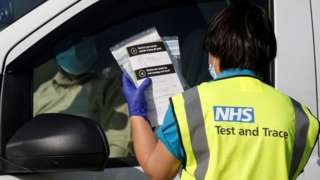 An NHS test and trace worker takes a coronavirus test to someone waiting in a vehicle