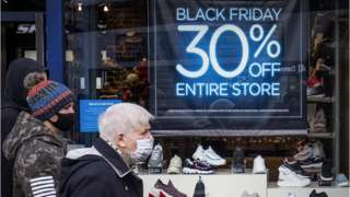 man outside store offering Black Friday discount