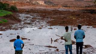 People survey the damage after the dam burst in Brazil