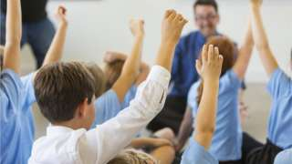 Excited school children in school uniform with hands up ready to answer a question from the teacher