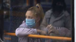 A woman looks out of the window of a bus