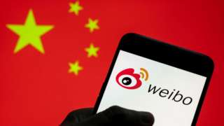 Chinese social media platform Weibo logo seen on an Android mobile device with People's Republic of China flag in the background.