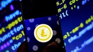 Litecoin logo on a phone in front of computer code