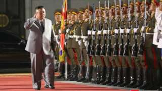 Kim Jong-un salutes as he walks past troops, Pyongyang (10 Oct)