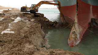 A digger removes sand and mud from the bow of the Ever Given, which ran aground in Egypt's Suez Canal (25 March 2021)