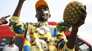 A fruit seller in a Minions shirt holds up pineapples in Abuja, Nigeria - Thursday 9 April 2020
