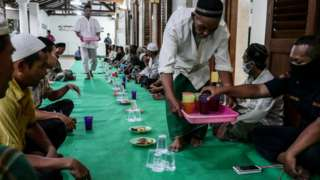 Residents Iftar together at An-Nawier Mosque on the first day of Ramadan during a large-scale social restriction (PSBB) as preventive measures for the spread of the coronavirus (COVID-19) in Jakarta, Indonesia