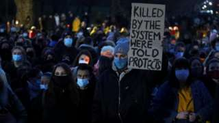 """A woman at the gathering in Clapham Common hold a sign that reads: """"Killed by the system we're told protects"""""""