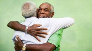Two elderly men wey dey hug