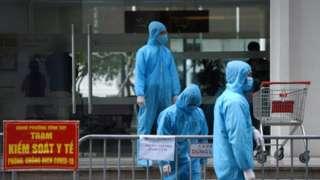 Nhân viên y tế mặc đồ bảo hộ đứng bên ngoài một tòa nhà được cách ly ở Hà Nội, Việt Nam, ngày 29 tháng 1 năm 2021