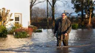 Gabrielle Burns-Smith outside her flooded home on the outskirts of Lymm in Cheshire