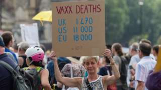 Woman holds a sign claiming vaccines are causing deaths