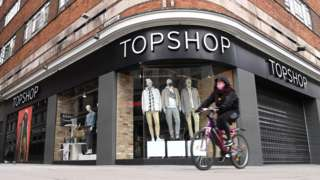 A woman in a mask cycles past a closed Topshop store
