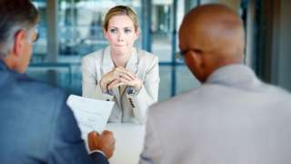 Mulher sendo entrevistada por dois homens para vaga de emprego