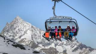 Skiers, some with face masks against the spread of Covid-19, ride a ski lift above Zermatt in the Swiss Alps, 28 Nov 20