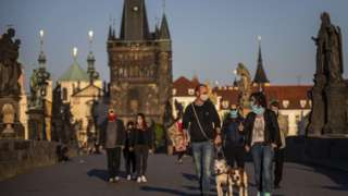 Pedestres de máscara andando em rua história de Praga