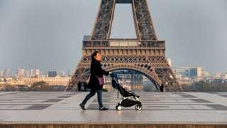 امرأة تسير وهي تجر عربة ابنها أمام برج ايفيل في باريس