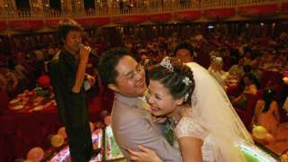 중국의 결혼식 만찬에서 서로를 껴안고 있는 신혼부부