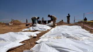 Iraqi forensic personnel exhumes bodies at a mass grave where inmates of Badoush prison were killed by the Islamic State group, in al-Humaydat village, western Mosul, Iraq (13 June 2021)
