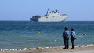 Papua New Guinea police officers on the foreshore watch an Australian warship off the coast