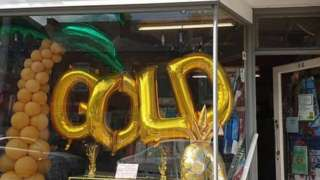 Shop front decorated with gold balloons