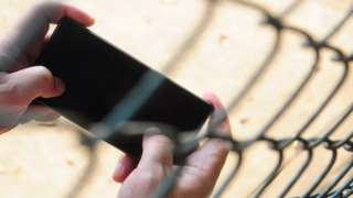 A mobile phone held inside wire fencing