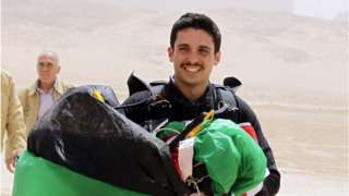 """Jordanian Prince Hamzah bin al-Hussein, president of the Royal Aero Sports Club of Jordan, carries a parachute during a media event to announce the launch of """"Skydive Jordan"""", in the Wadi Rum desert in April 2011"""