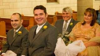 Francis, Basil, Charmagne e Shaul Goncalves sentados em igreja, aparentemente em casamento