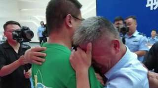 Guo Gangtang (R) is hugged by his long-lost son, who was snatched from him in China 24 years ago, 13 July 2021