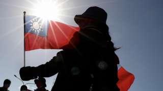 台北总统府前参加台湾双十节庆典的一位女士在阳光底下举起青天白日满地红旗拍照留念(10/10/2021)