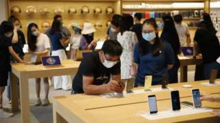 Customers visit the new Apple flagship store in Beijing, China, 17 July 2020. Apple opens its new flagship store in Beijing on 17 July, replacing its first store in China which opened in 2008