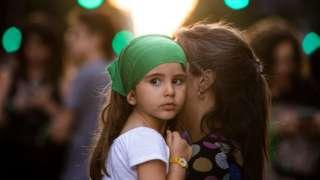 Una niña cargada por su madre.