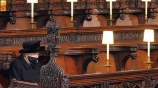 La reina Isabel II sentada en el interior de la capilla de San Jorge.