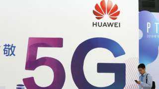 A man walking past a Huawei 5G sign