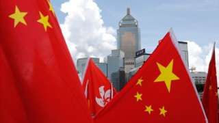 Buildings are seen above Hong Kong and Chinese flags, as pro-China supporters celebration after China's parliament passes national security law for Hong Kong, in Hong Kong, on 30 June 2020