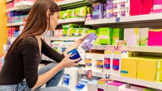 Young woman shopping for sanitary products